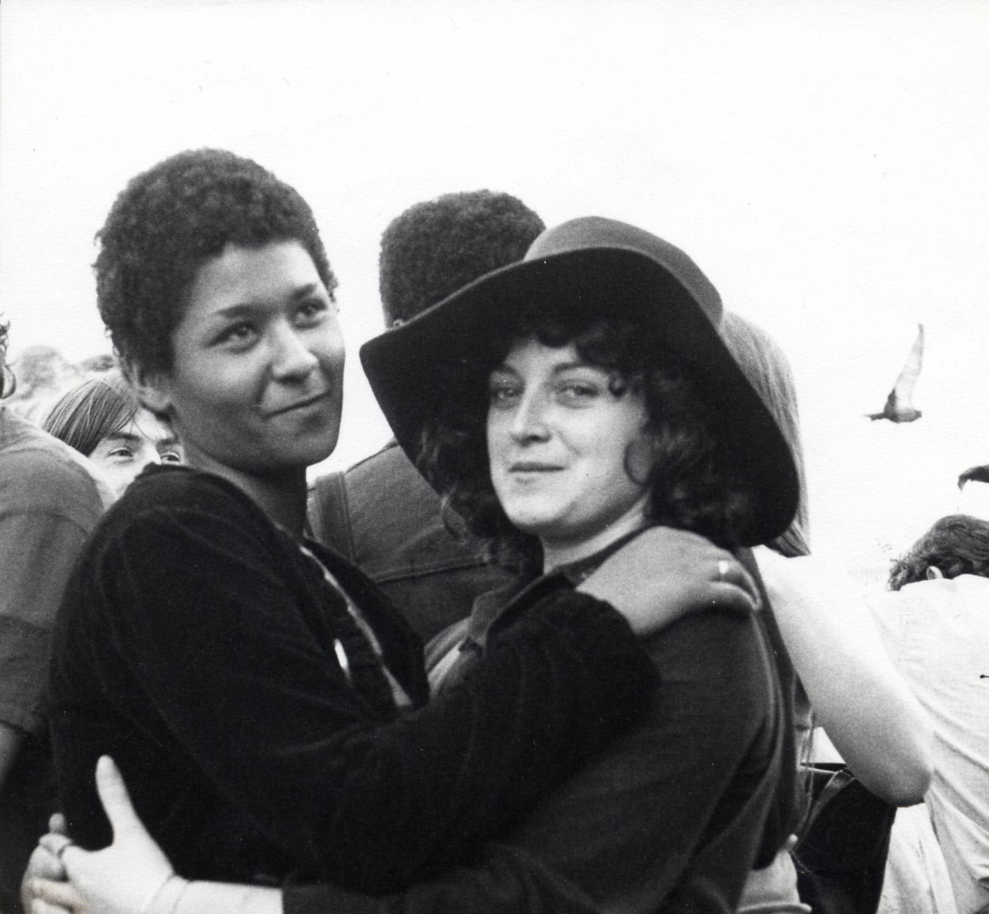 Two women, a Black woman and a white woman hold each other and smile at the camera during a Gay Liberation Front demonstration in 1972