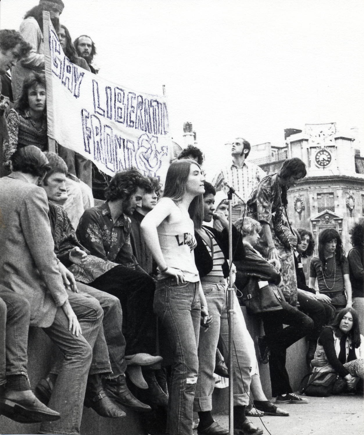 Black and white photo of a crowd, mainly young people, stand in Trafalgar Square, with a large Gay Liberation Front banner behind them. A woman speaks into a microphone,