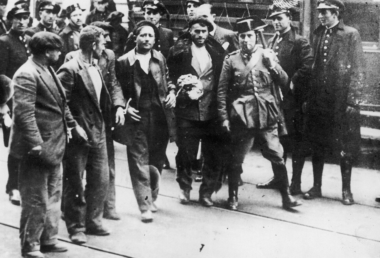 Black and white showing five men, tied together at the wrists, after being arrested. Policemen follow the men, or watch from the side of the road as they walk..