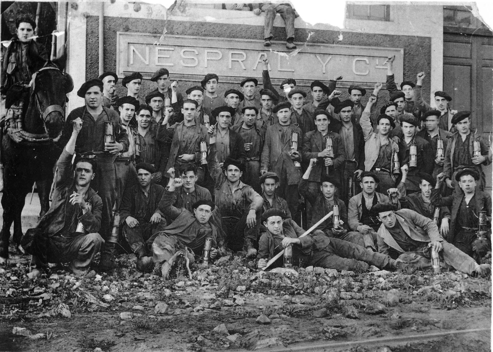 Black and white photo showing a group of c.50 workers, some with fists raised, others with tools or lamps in front of the Newspral Y Compania building in the early 1930s
