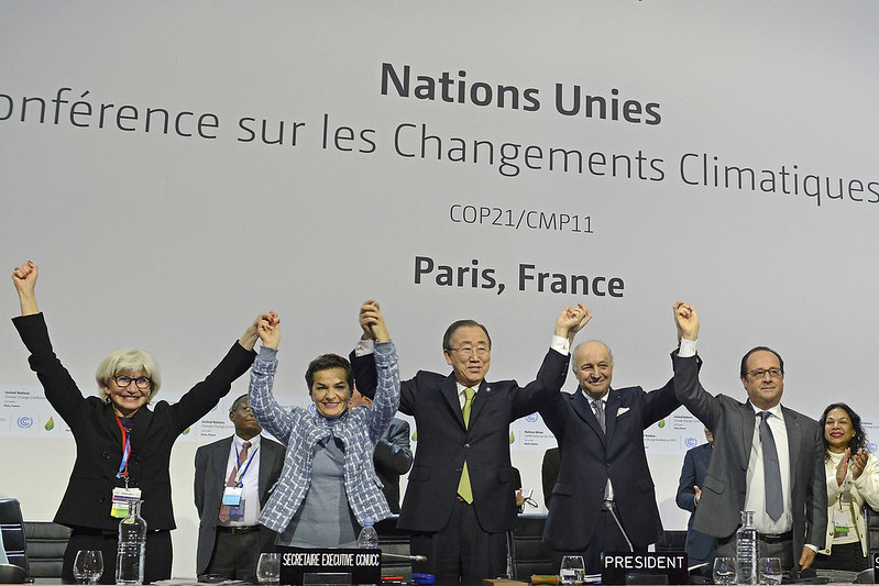 Ban Ki Moon and delegates raise their hands in celebration of the adoption of the Paris Accord, United Nations Climate Change Conference, 2015