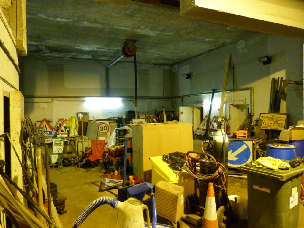 Inside view of the nuclear bunker housing the Highlands Council Road Depot. Road signs, tools and machinery fill the concrete room. A couple of plastic chairs hint at tea breaks sheletered from the rain and midges.