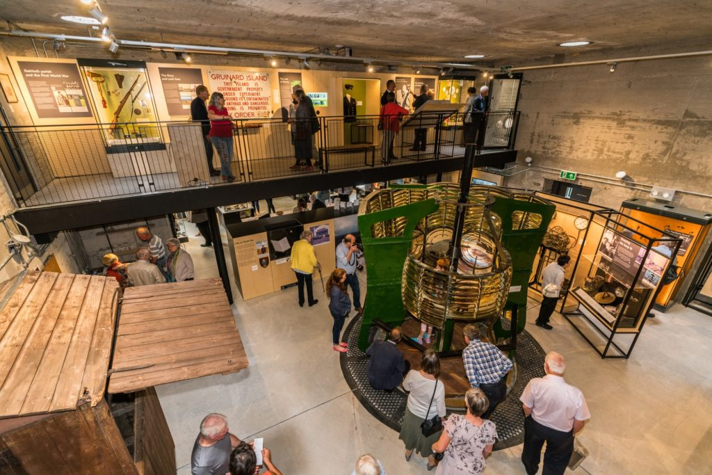 Image shows the new museum interior, with the original lens from Rubh Re lighthouse in the centre. Visitors view the exhibits, including on the original mezzanine walkwat that would have looked over the anti-aircraft operations room.