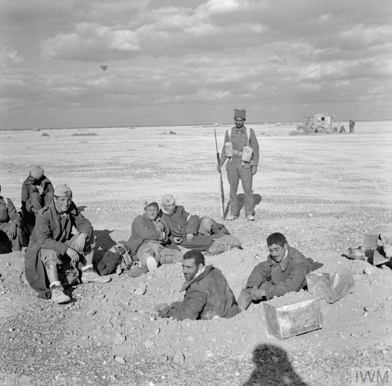An Indian soldier guards a group of Italian prisoners near El Adem aerodrome, during the pursuit of Axis forces westwards after the relief of Tobruk.