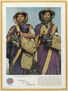 two Indian women of the Auxiliary Ambulance Service, wearing purple saris and tin helmets.