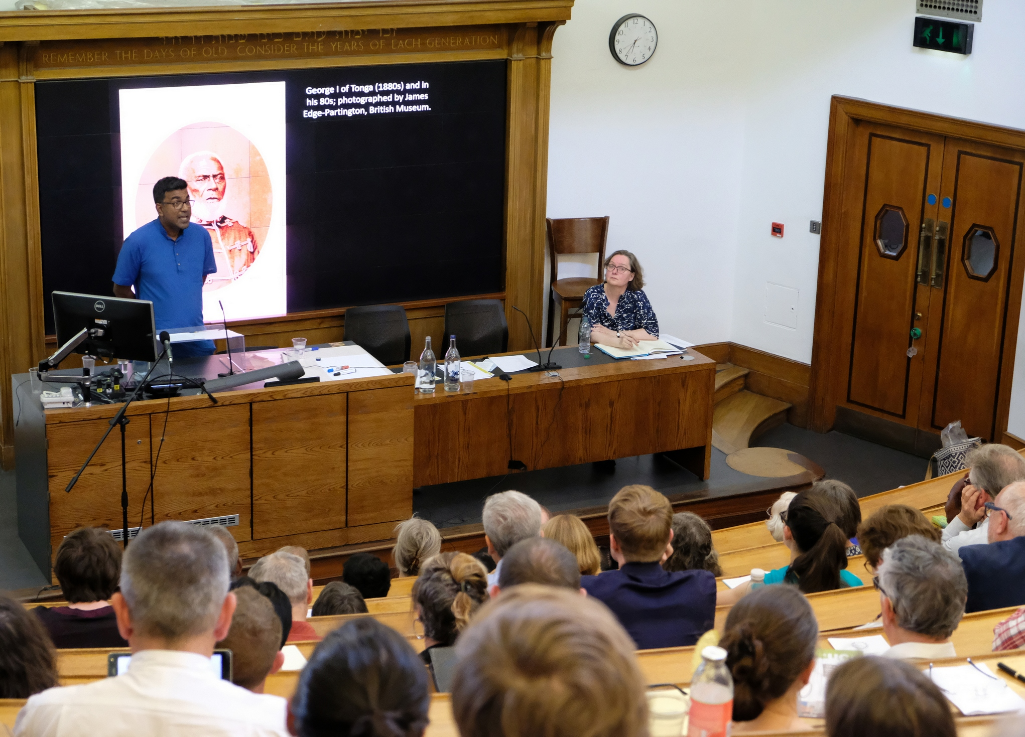 Dr Sujit Sivasundaram stands in from of his presentation as he speaks to a large audience in the image foreground. Professor Margot Finn, the chair of the event sits to the speaker's right.