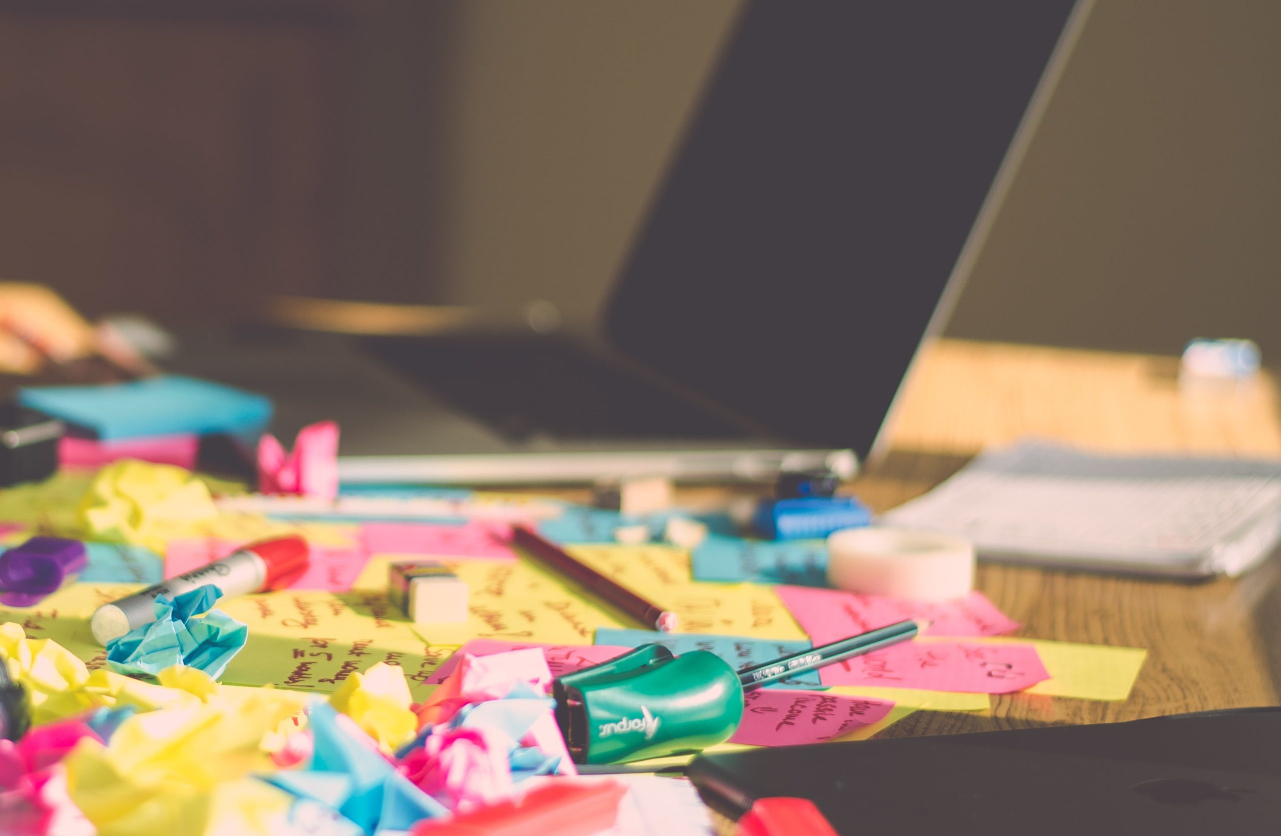 A laptop in the background is surrounded by multi-coloured screwed up post it notes.post it notes
