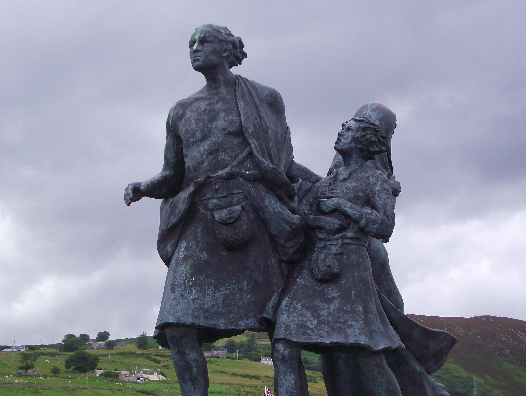 """Emigrants Statue at Helmsdale Sutherland Scotland Behind the statue is Marrel Hill (Creag Marail) and the crofts on the steep brae of West Helmsdale. """"The Emigrants commemorates the people of the Highlands and Islands of Scotland who, in the face of great adversity, sought freedom, hope and justice beyond these shores. They and their descendants went forth and explored continents, built great countries and cities and gave their enterprise and culture to the world. This is their legacy. Their voices will echo forever thro the empty straths and glens of their homeland."""" Thus reads the inscription on the """"The Emigrants"""" statue in Couper Park, overlooking the village (and harbour) of Helmsdale in the Parish of Kildonan and the County of Sutherland in Northern Scotland. The statue depicts a kilted father leading his child forward towards the North Sea, while the mother looks back wistfully at the Strath (Gaelic: wide valley) of Kildonan from whence they have come."""
