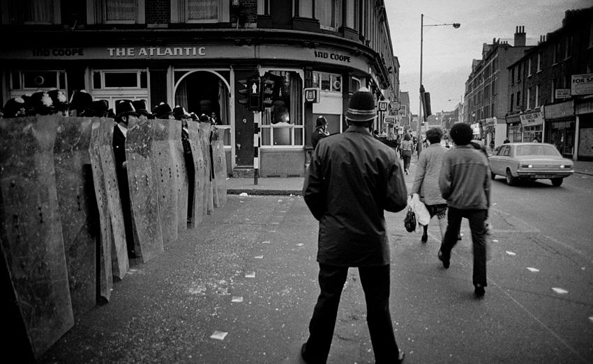 11 April 1981, during the 1981 Brixton riot in London, police with riot shields line up outside the Atlantic Pub, on the corner of Atlantic Road and Coldharbour Lane, Brixton.