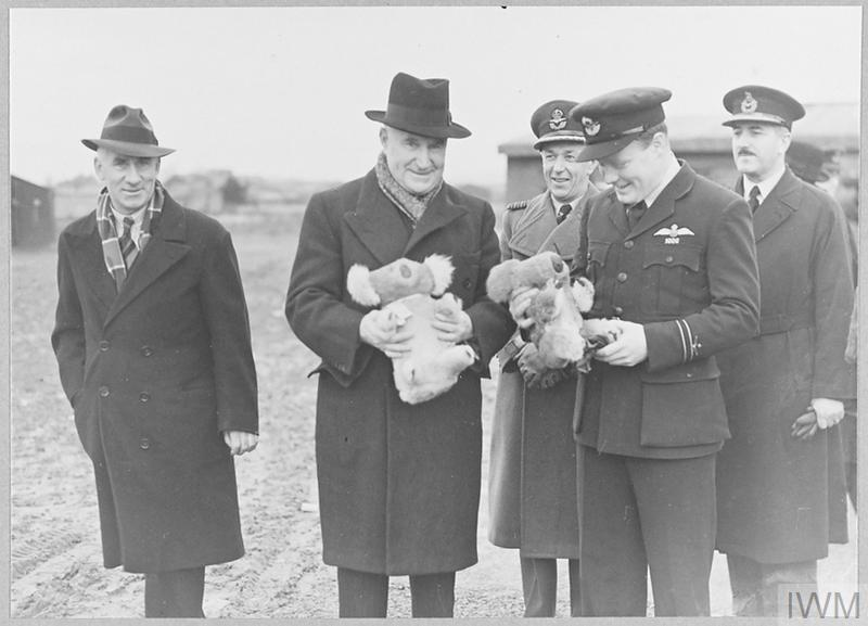Australian Envoys hold koala bear stuffed toys on visit to Australian Air Force in Britain during WW2.